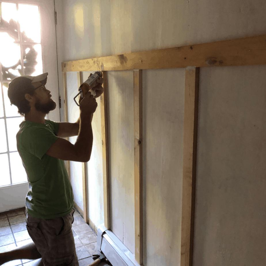 man caulking boards on wall