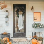 front porch decor with mums, pumpkins, and fall sign