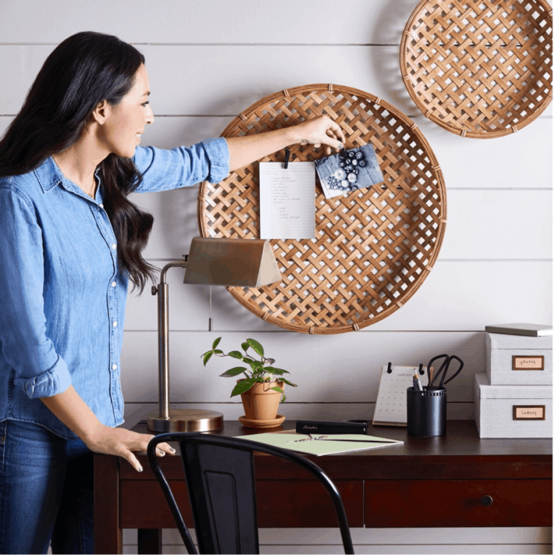 Joanna Gaines hanging up pictures on a wall basket as an organizer