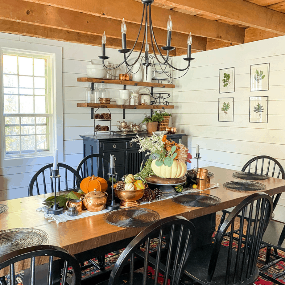 large dining room table with pumpkins in centerpiece, large exposed beams, and open shelving with kitchen are on shelf