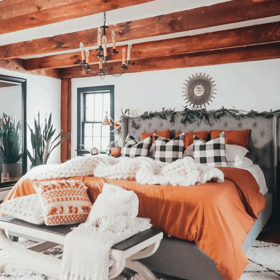 rust colored bedding with buffalo plaid pillows and exposed beams on the ceiling