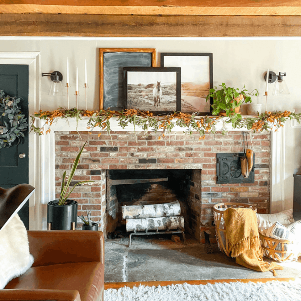 brick fireplace with horse picture on mantel and fall garland