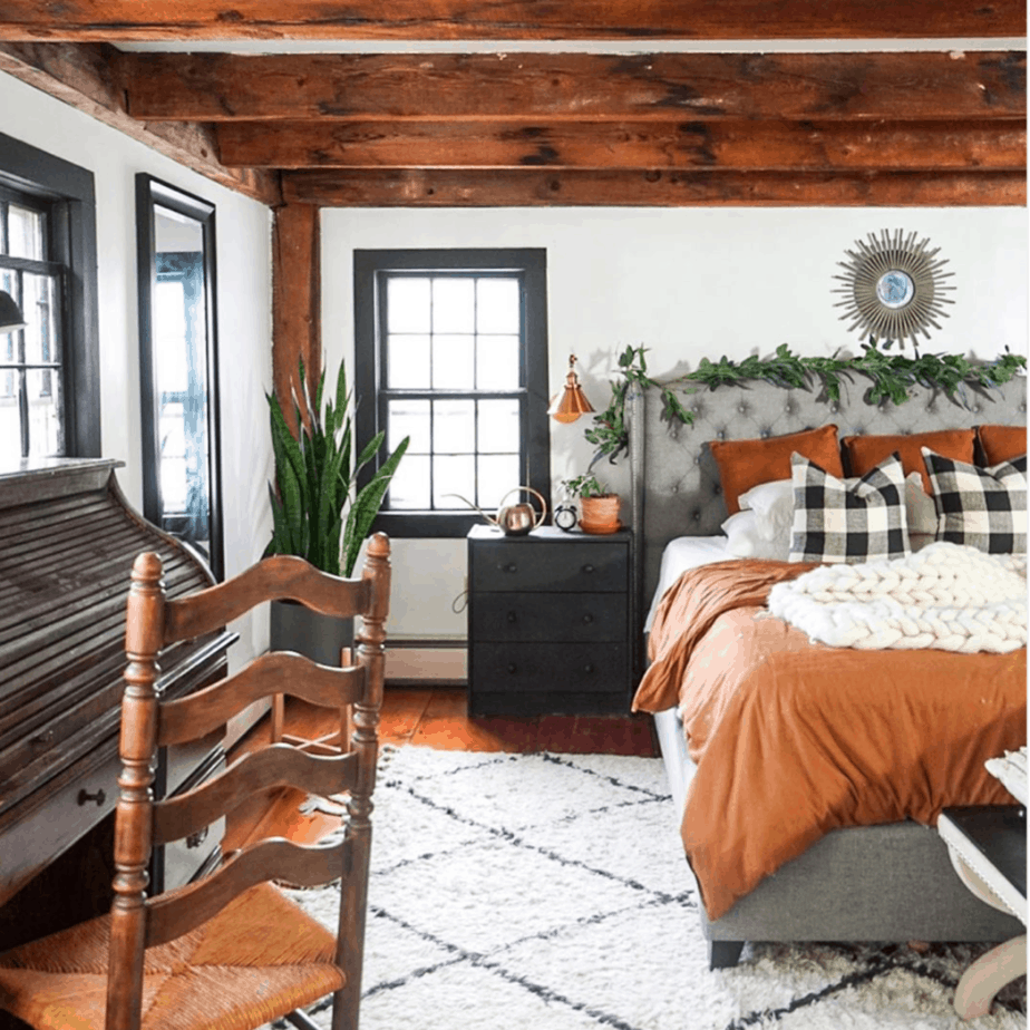 farmhouse bedroom with exposed wooden beams and rust colored bedding. wooden secretary desk and wooden chair. buffalo plaid pillows and white knit blanket on bed.