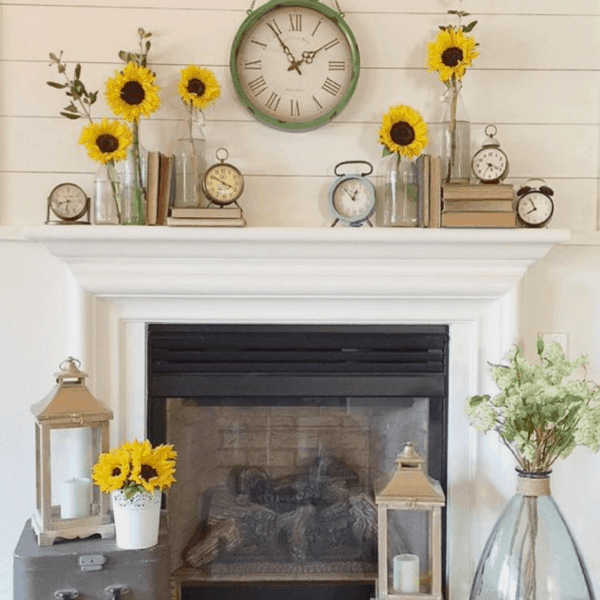sunflowers in glass jars on top of a white mantel