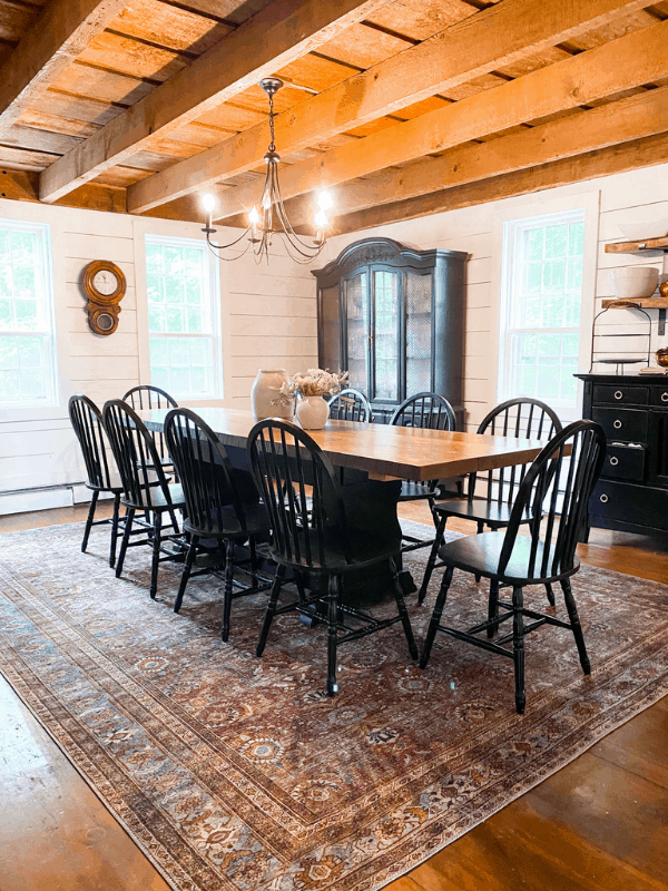 Farmhouse style dining room with black chairs, exposed beams, and shiplap on walls.