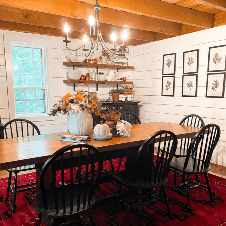 dining room decorated for Fall with. red rug, wooden table, and black chairs.