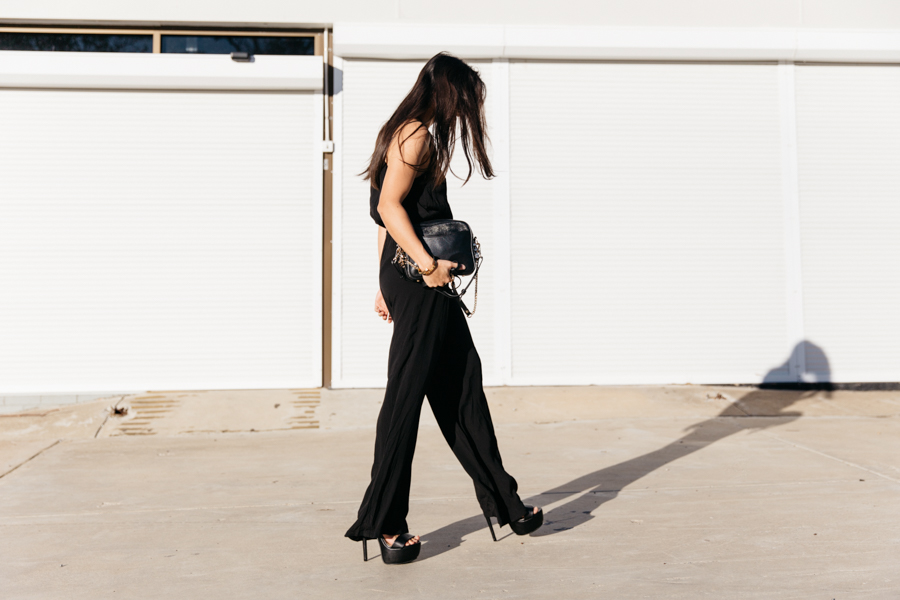 Corporate outfit wearing a black jumpsuit with flared pants.