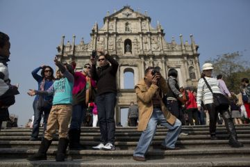 Tourists take photographs in front of the Ruins of St. Paul's Cathedral in Macau
