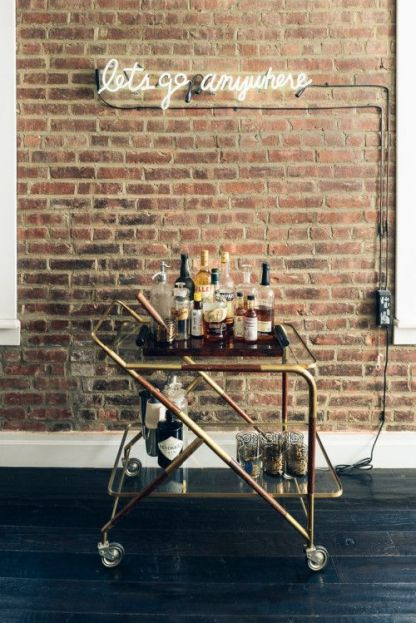 brick neon sign and bar cart