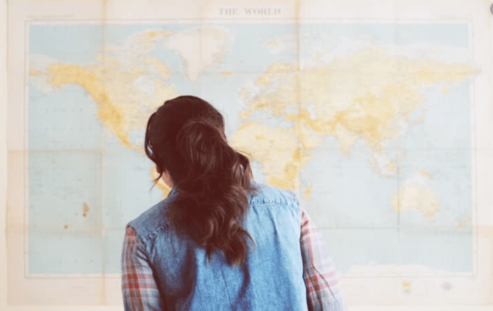 Girl looking a at world map wondering which place should she visit next