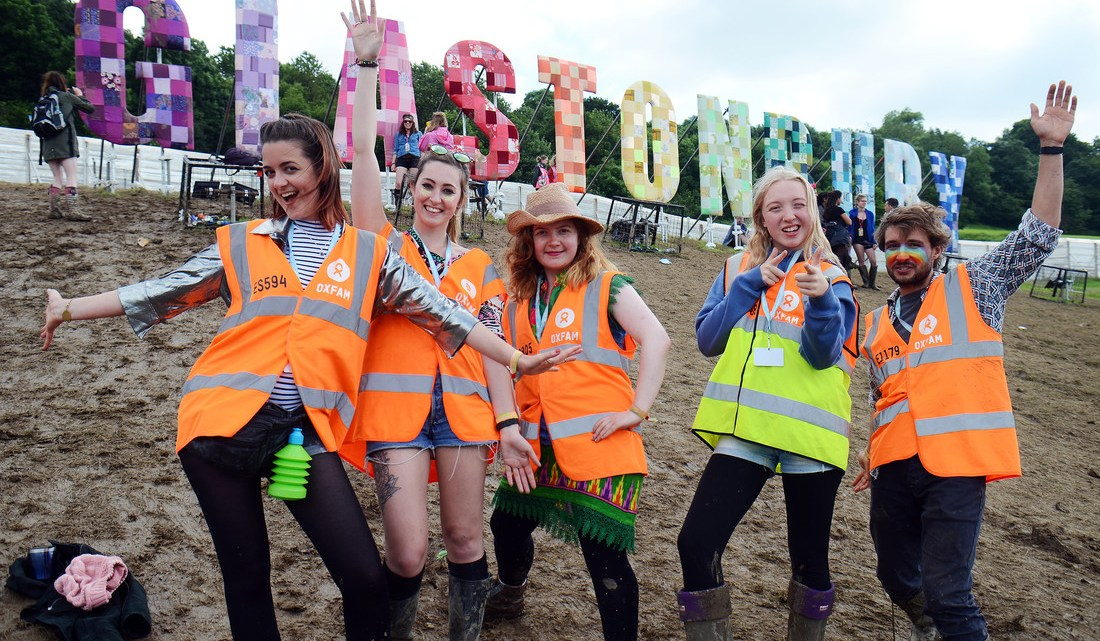 Oxfam stewards smile for the camera in front of the Glastonbury sign.