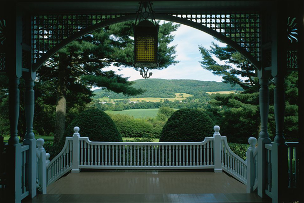 Marsh-Billings-Rockefeller National Historical Park in Woodstock, Vermont; view from the east entry door across the veranda and the big meadow of the Billings Farm and Museum to Blake Hill. Photographed by Jack E. Boucher, 2002; HALS Field Supervisor, Norma Williams. (Library of Congress, Prints & Photographs Division, HALS, HALS VT-1).