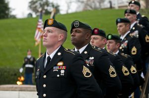 """Special Forces Green Beret soldiers from each of the Army's seven Special Forces Groups stand silent watch during the wreath-laying ceremony at the grave of President John F. Kennedy, Nov. 17, 2011 Image Source: """"Seven Green berets"""" by U.S. Army"""