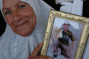 Mother hold photo of child being held under administrative detention.  Image Source: Lisa Nessan, Flickr, Creative Commons