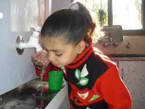 Image Source: Middle East Children's Alliance, Flickr, Creative Commons Maghazi Girl A kindergartener in Maghazi Refugee Camp, Gaza drinks clean water from a Maia Project unit installed in Dec 2009 thanks to supporters in Granville, Ohio. Credit: Mohammed Majdalawi