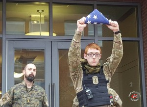 A member from the Ohio group SHTF presents the folded flag, honoring Lavoy Finicum, to a silent crowd of 55 in Columbus, Ohio.