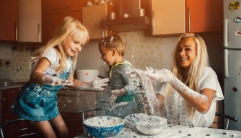 family fun mother and children playing on kitchen with flour