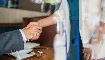 woman shaking mans hand interview job