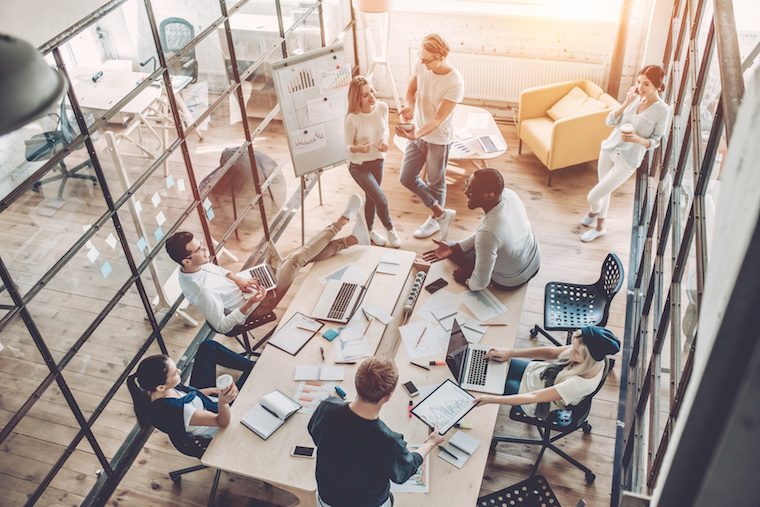 Top view of multiracial young creative people in modern office. Group of young business people are working together with laptop, tablet, smart phone, notebook. Successful hipster team in coworking. Freelancers.