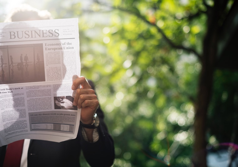 man holding newspaper green, responsible investment