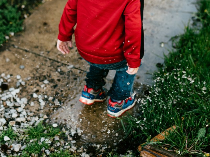 kid jumping in puddle raining