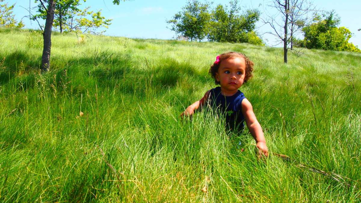 girl in long grass symbol of climate emergency