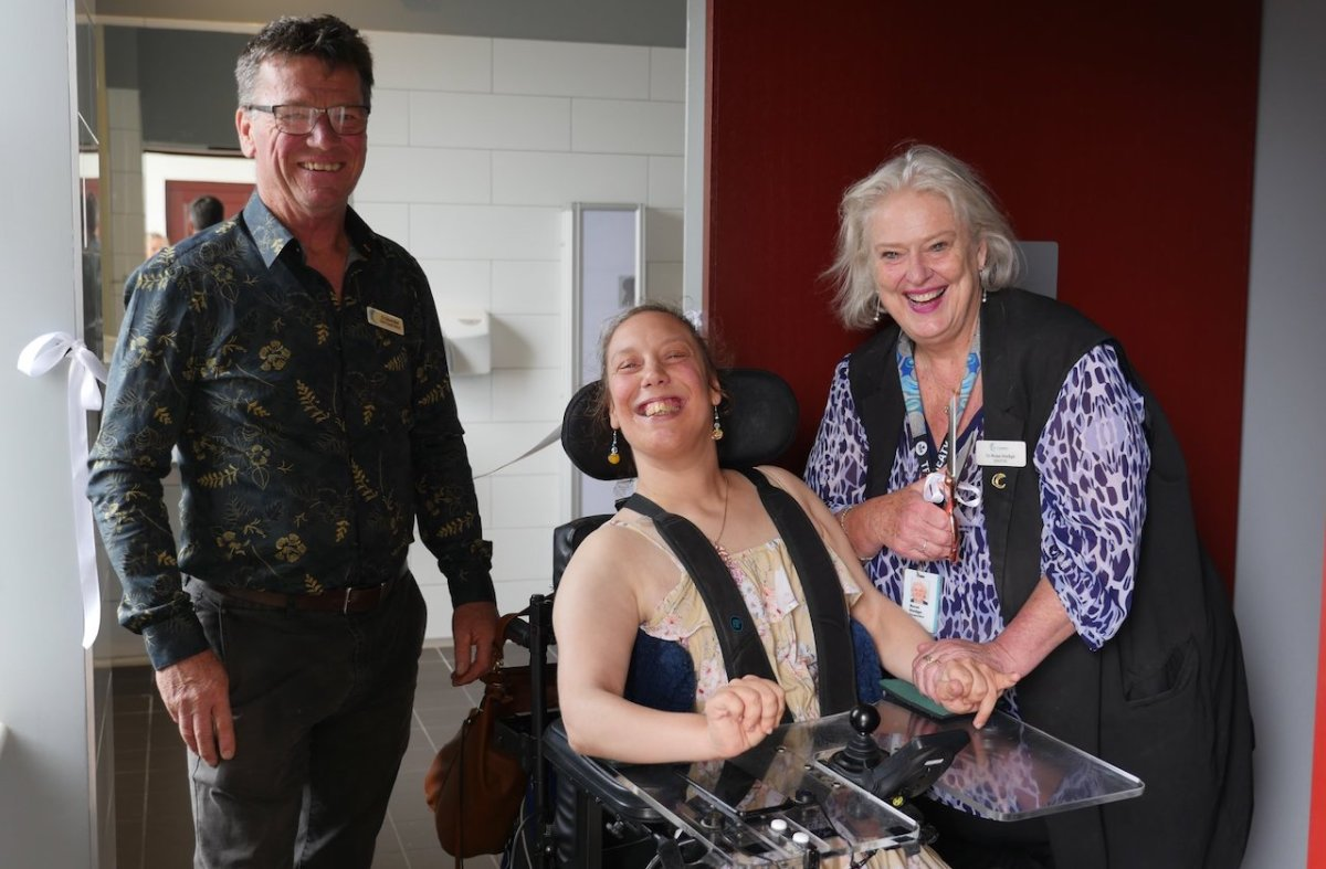 woman in wheelchair smiling with man and woman