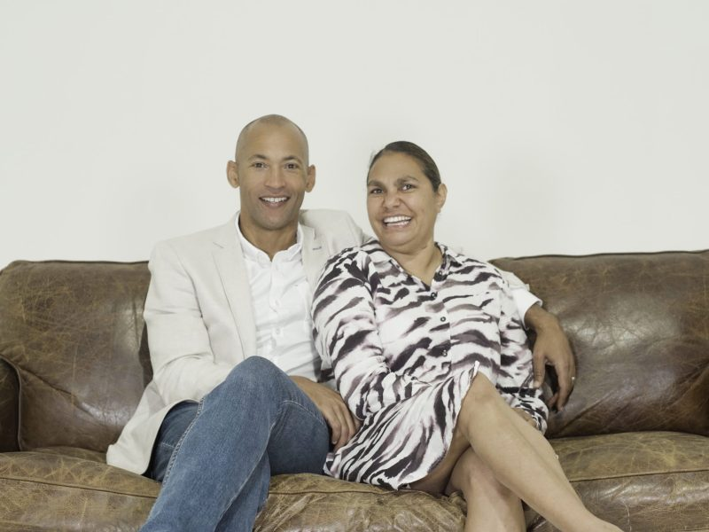 husband and wife smiling, sitting on sofa