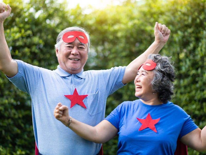 Senior couple in Superhero costume relaxing and celebrating with victory. Elderly people wear red masks and blue shirt with stars having fun, smiling at the park outdoor togetherness.