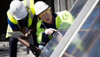 Two Caucasian Engineer Discussing and Checking Solar Panels