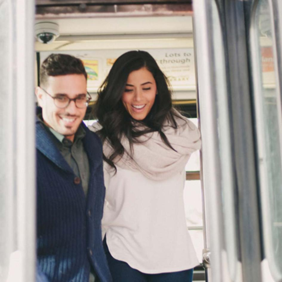 a man and woman getting off a train smiling
