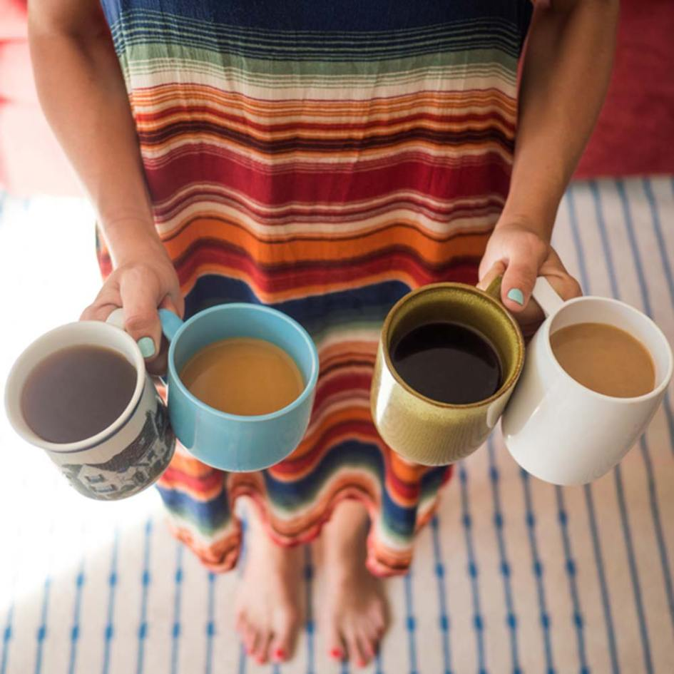 a woman holding four cups of coffee