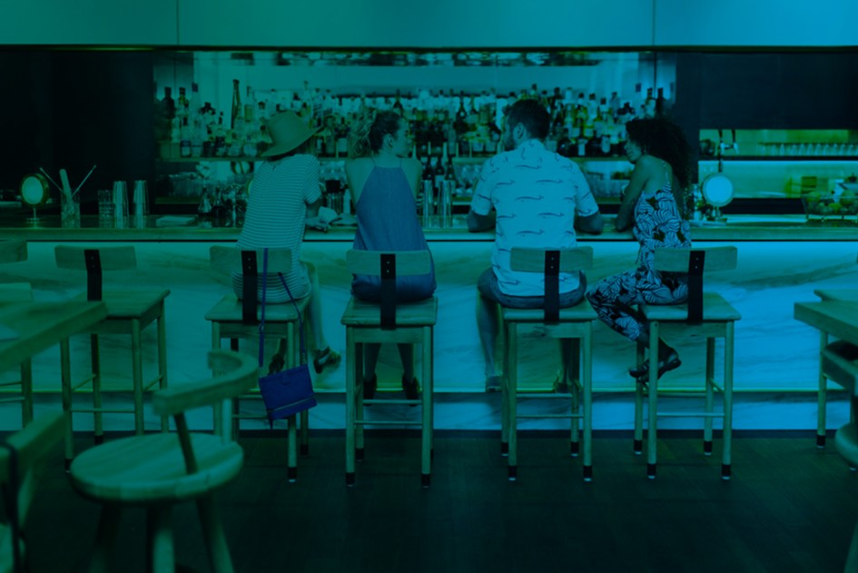 Group of four friends sitting at a cocktail bar with their backs to the camera.
