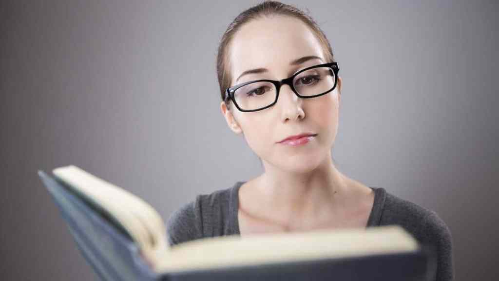 a millennial woman reads a book about investing