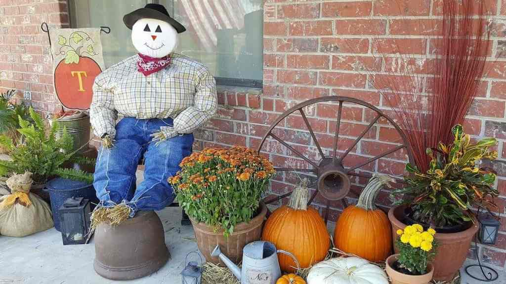 a scarecrow outside a home at thanksgiving