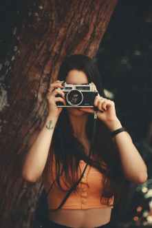anonymous woman with photo camera in forest