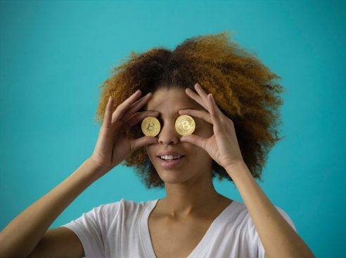 A lady holding Bitcoins to her eyes
