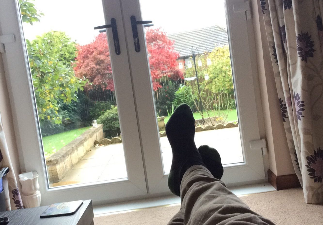 Evocative image: the editor's feet stretched out, big windowed doors, a fresh, bright garden outside.