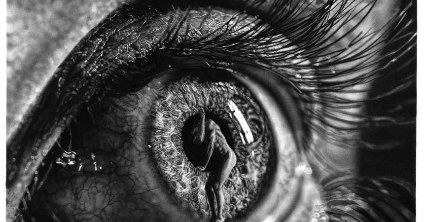 Extreme close-up of an long-lashed eye. A naked man clambers through the pupil.