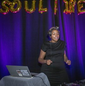 A black woman in a black dress and wearing headphones is pictured dancing in front of a laptop and under gold metallic balloons hanging on purple curtains.