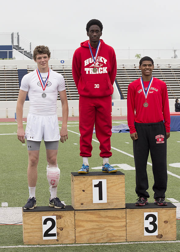 Josh Nowell of Stephenville, left, accepts his silver medal for finishing second in the long jump in Graham Thursday. || Dr. CHET MARTIN