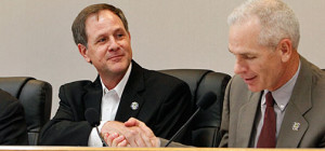 Newly reelected Mayor Pro Tem Russ McDanel, left, receives a congratulatory handshake from Mayor Kenny Weldon.    RUSSELL HUFFMAN/TheFlashToday.com
