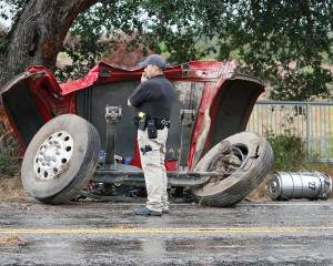 A deputy stands in front of the 18-wheeler's front axle and tires. The truck collided with the live oak tree in the back ground.