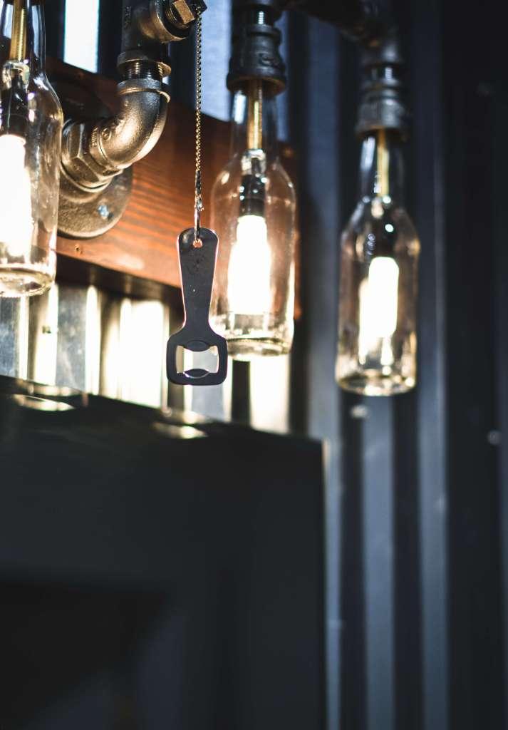 Bottle opener hanging from lights on bathroom vanity at the Beer Spa