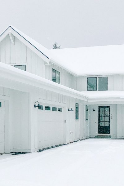 white farmhouse covered in snow