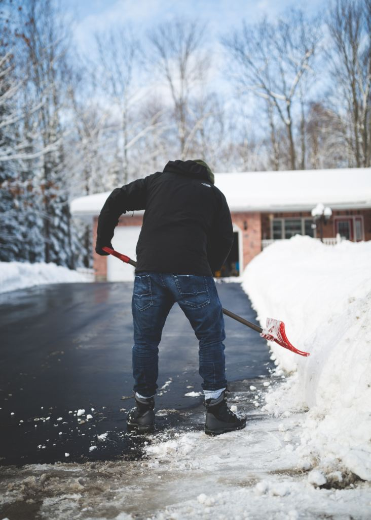 shoveling snow to create a walkway to house