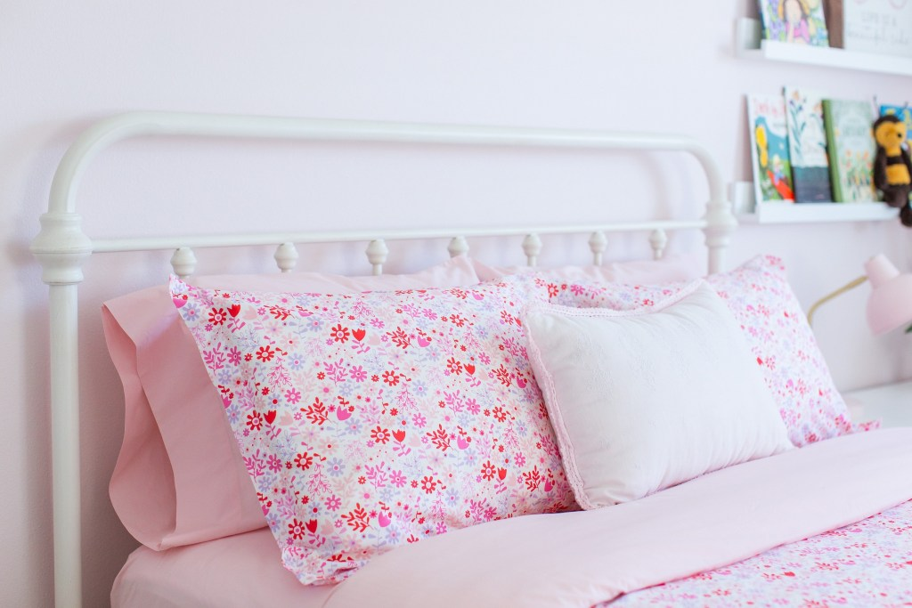 A pink floral themed girl's bedroom. Find inspiration for your daughter's bedroom. Pink flowers give this bedroom a cheerful floral vibe.