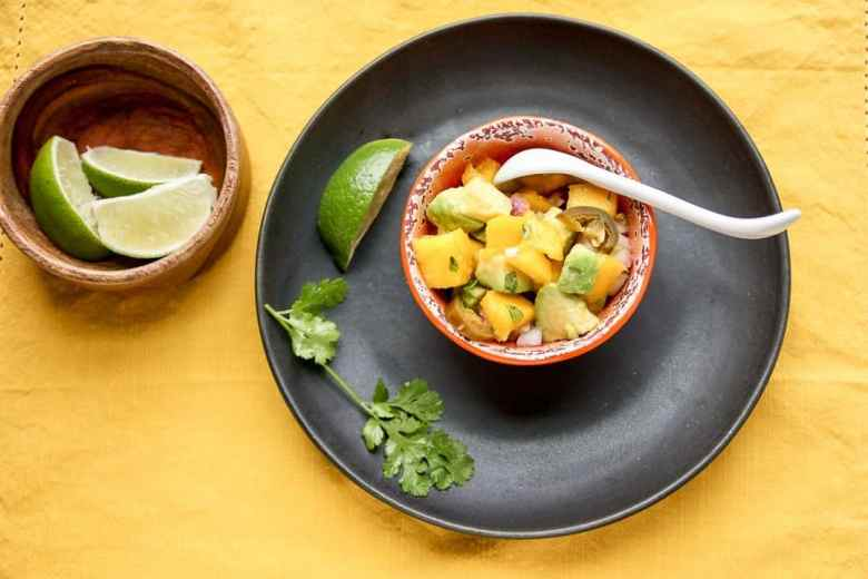 Mango Avocado Salsa in an orange bowl on a black saucer on a yellow table cloth with a sprig of cilantro and a small wooden bowl of lime wedges.