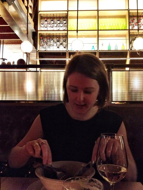 a girl eating at Agricola Street Brasserie in the dimly lit restaurant
