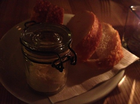 A plate of warm french bread with whipped butter in a jar